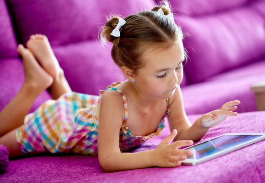 Little girl with a tablet computer on a sofa at home