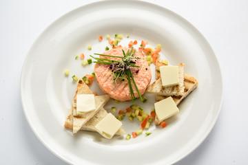 Fresh tartar with salmon, cucumber  on white plate,