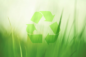 Lovely sunny blurred meadow with recycle symbol. Conceptual green clean environment background.