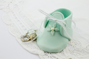 Blue baby fondant sugar bootees on white lace background with silver charms