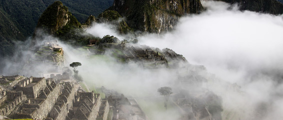 Atmospheric panoramic view to terraces hovered by morning clouds, Machu Picchu, Unesco World Heritage site, Sacred Valley, Peru