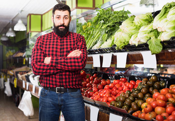 Male seller standing  near the shelves  in grocery shop