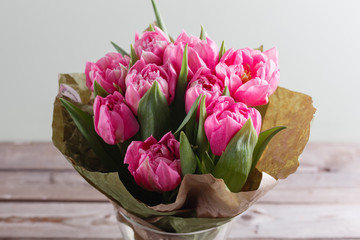 Bouquet of pink peony tulips on a wooden background. Spring flowers. Mother's Day background.