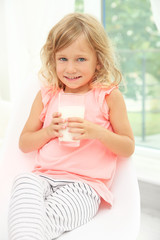 Portrait of little girl with glass of milk