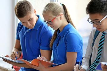 Classmates standing near window