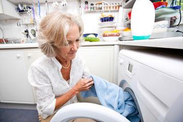 Senior woman loading washing machine at home