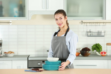 Woman in apron holding dishes on kitchen table