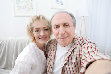 Happy senior couple making selfie at home