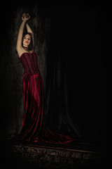 Portrait of beautiful lonely gothic vampire woman in long red dress in the dark castle