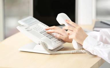 Woman dialing number on telephone in office