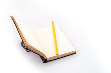 Open empty diary with yellow pencil on table