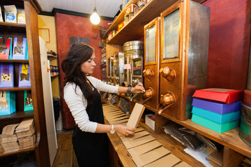 Side view of salesperson dispensing coffee beans into paper bag at store