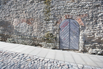 Ancient door by cobblestone street, Tallinn, Estonia, Europe