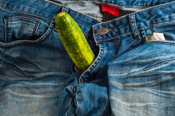 Big green cucumber in jeans fly as concept of man health and strong