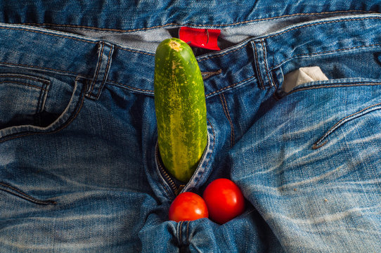 Green cucumber and two red tomatoes in jeans fly as concept of man health and strong