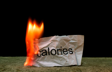 Word calories on crumpled piece of paper burn. Concept of Burn your calories and health care life style
