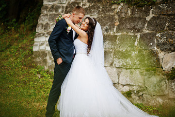 Young stylish wedding couple against old stone wall.