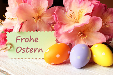 Rhododendron-Blüten mit Ostereiern auf weißem Holztisch mit Schildchen Frohe Ostern, Blumenstrauß