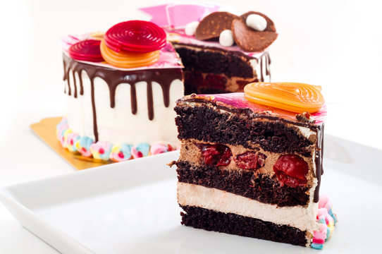 Side view to slice of piece of Sweet and colorful chocolate birthday cake with bright and vivid candy