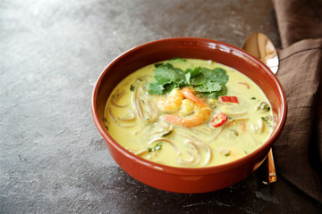 Spicy soup with coconut milk, noodles and shrimps. Eastern cuisine
