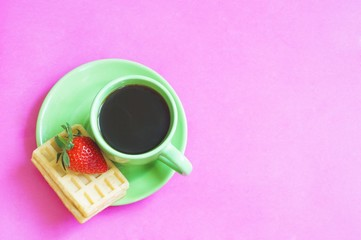 Flat lay food photography/ Green cup of coffee and waffle with strawberries on a pink background