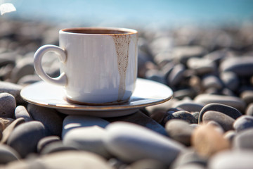 A cup of spilled coffee stands on stones near the sea shore