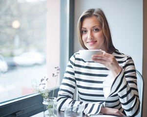 Portrait of smiling woman having coffee at cafe table