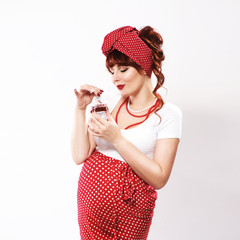 Fashionable redhead pregnant woman in pin up style sniffs perfume