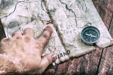Man point by finger to red cross on vintage old fake pirate map of Treasures. Adventure time
