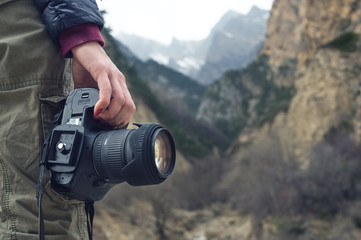 A female hand holds a camera against a mountain landscape