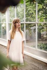 Gorgeous woman in garden by window