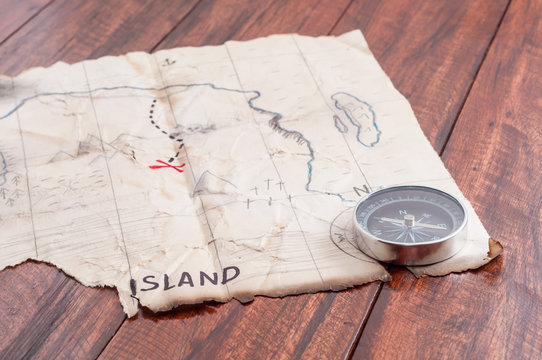 Treasure Map of fake Island with compass and red cross on wooden table background. Adventure concept