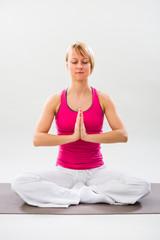 Woman exercising yoga indoor,Lotus position/Padmasana