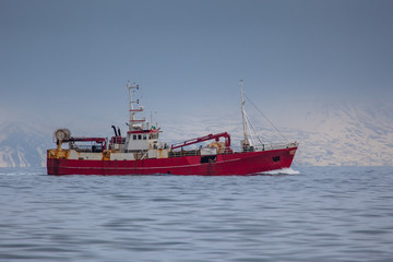 Commercial fishing boat sailing near the coast of Iceland.