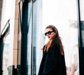 Fashion photo of beautiful young woman with sunglasses. Model looking at camera. City lifestyle. Female fashion.