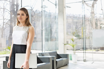 Portrait of confident businesswoman holding laptop while standing at office lobby