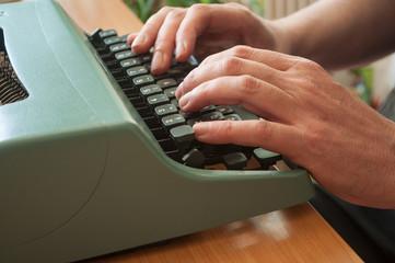 détail mains d'homme sur clavier de machine à écrire ancienne