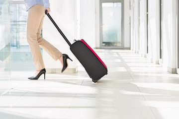 Low section of businesswoman with luggage exiting airport