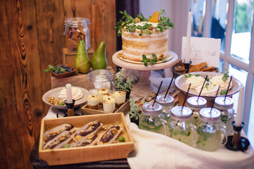 sweet bar with eclairs, lemonade,sweets and white cake  decorated with greenery in area of wedding party
