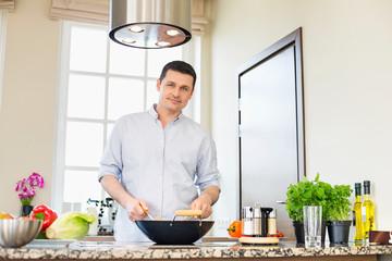 Portrait of confident man preparing food in kitchen