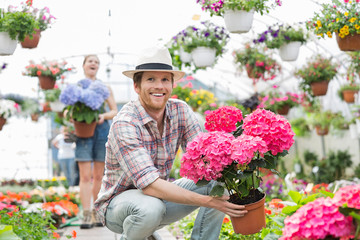 Happy gardener holding flower pot with colleague standing in background at greenhouse