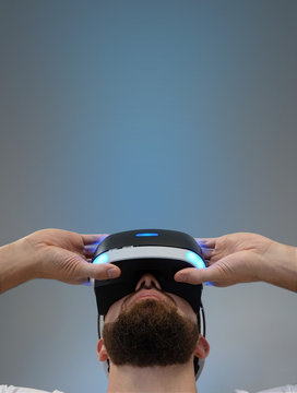 Young man with a beard looks at 3D glasses. A man in virtual glasses is looking up, above him is a blue glow. Type of shooting from below. Empty copy space for text.