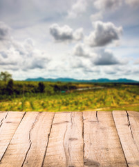 Plank wooden table in front of blurred landscape background