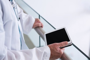 Doctor using a digital tablet in the passageway at hospital