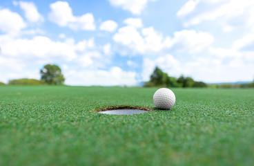 Golf ball near hole, background blue sky..