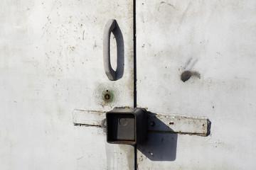 Grey metal garage door with padlocks handle
