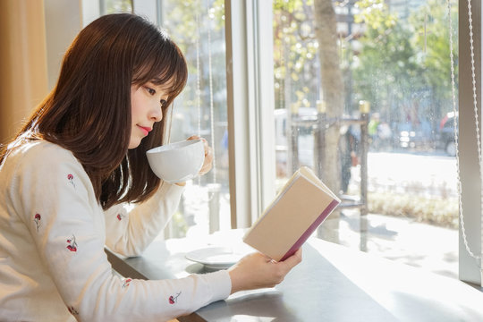 カフェで読書をする若い女性