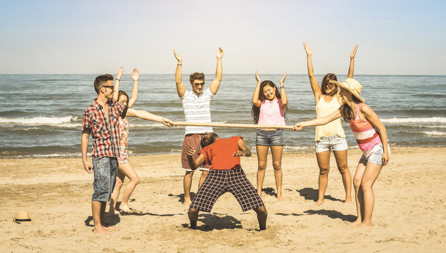 Multiracial happy friends group having fun together with limbo game at beach - Summer joy and friendship concept with young multi ethnic people playing on spring break vacation - Retro vintage filter