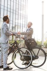 Businessmen shaking hands outside office building