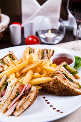 Four sandwiches on the plate with french fries.